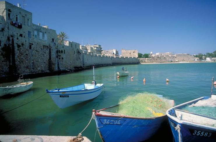 Fishing boats in the bay, with the old Mediterranean sea wall