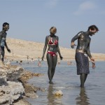 Tourists covered with mud, at a Dead Sea beach 